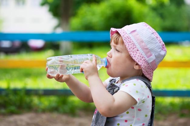 Bambino beve dalla bottiglia di plastica
