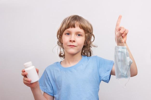 Bambino biondo in maglietta blu che tiene maschera medica e barattolo bianco con medicina in sue mani. prevenzione della diffusione dell'infezione da virus e concetto di contaminazione