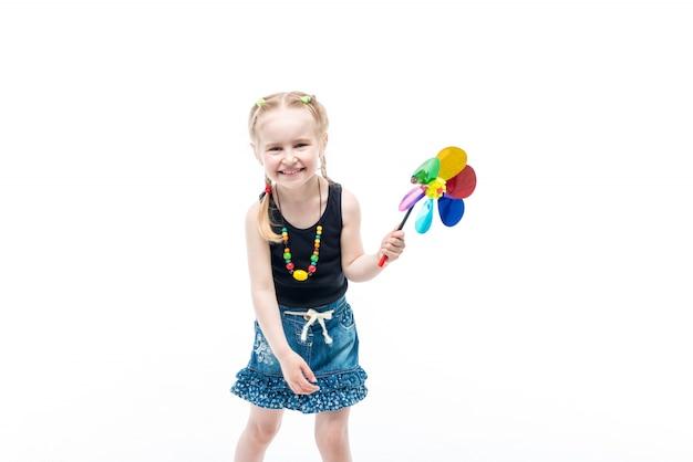 Bambino biondo sorridente con il tanktop da portare del giocattolo di filatura