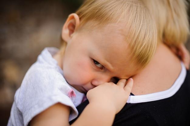 Bambino biondo sveglio che si trova sulla spalla della mamma