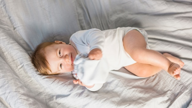 Bambino biondo sveglio di vista superiore in letto bianco