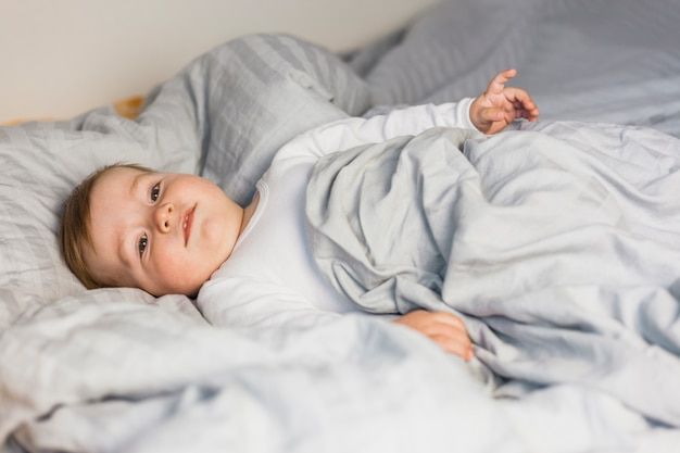 Bambino biondo sveglio in letto bianco con coperte