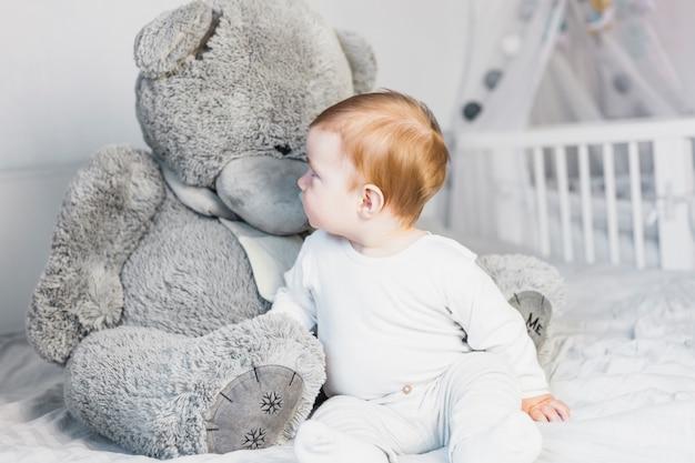 Bambino biondo sveglio in letto bianco con orsacchiotto