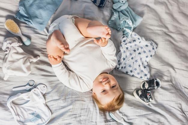 Bambino biondo vista dall'alto circondato da vestiti