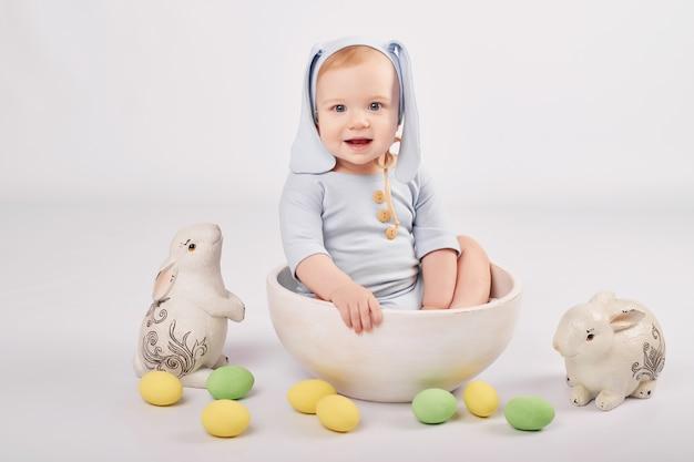 Bambino carino con coniglietti e uova di pasqua dipinte