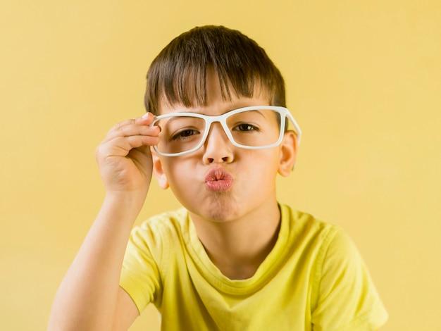 Bambino carino con gli occhiali e soffiando un bacio