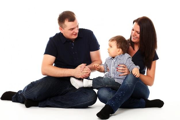 Bambino carino con i suoi genitori su bianco