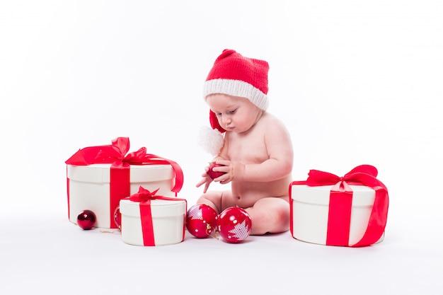 Bambino carino con regali di natale e cappello di babbo natale