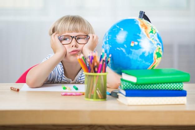 Bambino carino noioso sulla lezione. il bambino non vuole fare i compiti o fare i compiti. scolaro infelice.