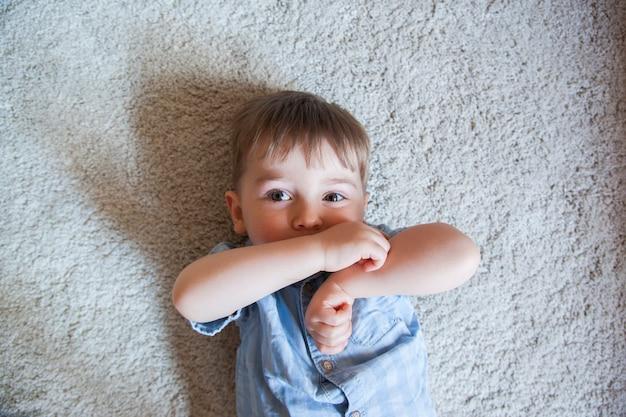 Bambino caucasico biondo che gioca i giochi isolati a casa.