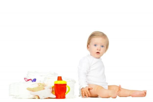 Bambino caucasico con pannolini impilati e giocattoli isolati su bianco