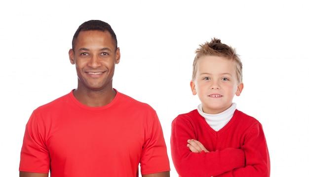 Bambino caucasico con uomo africano in rosso guardando la fotocamera