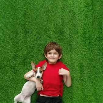 Bambino che abbraccia cucciolo jack russell e sdraiato sul tappeto verde.