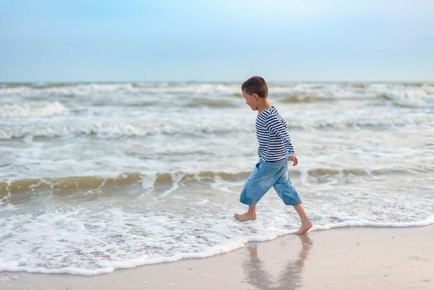 Bambino che corre sulla spiaggia. vacanze estive. bambino felice che gioca sulla spiaggia al momento del tramonto
