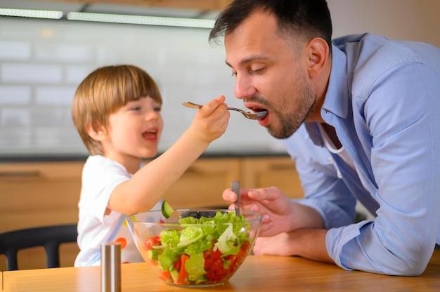 Bambino che dà a suo padre l'insalata da mangiare
