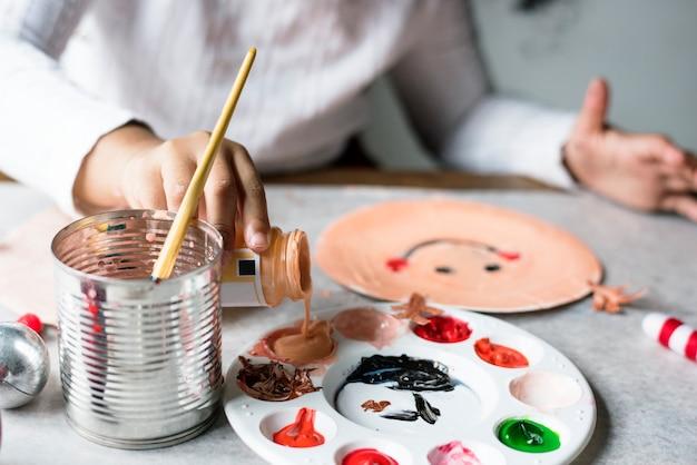 Bambino che dipinge babbo natale su un piatto di carta