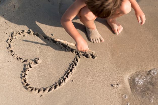 Bambino che disegna un cuore nella sabbia