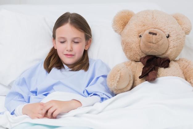 Bambino che dorme con un orsacchiotto mentre si trova in un letto