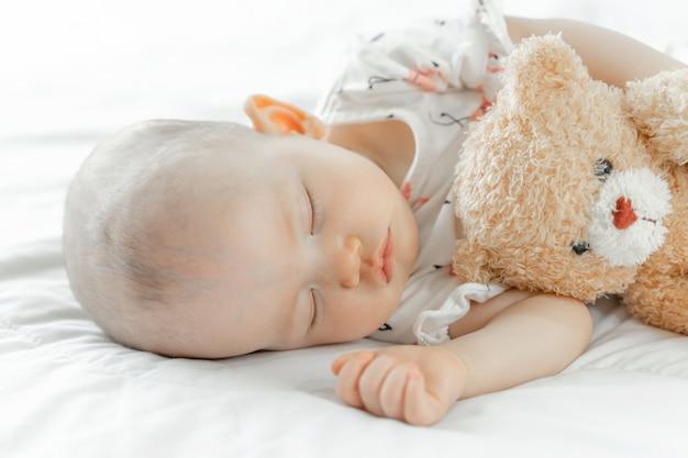 Bambino che dorme con un orsacchiotto