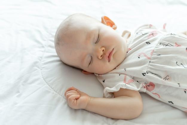 Bambino che dorme su un letto bianco