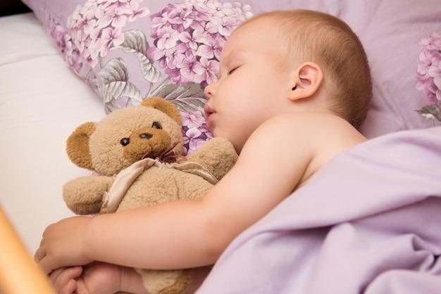 Bambino che dorme sul letto con teddy