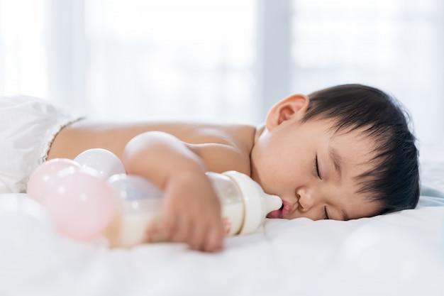 Bambino che dorme sul letto dopo aver bevuto il latte in bottiglia