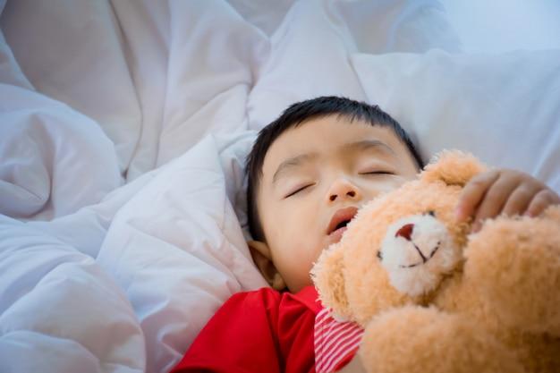 Bambino che dorme sul letto in camera da letto.
