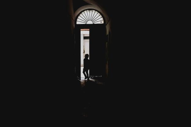 Bambino che esce attraverso una porta retroilluminata, concetto di solitudine e assenza durante l'infanzia.