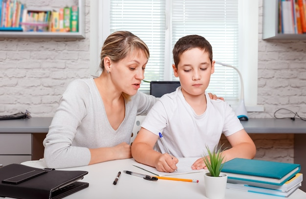 Bambino che fa i compiti a casa con i libri. istruzione, istruzione domiciliare