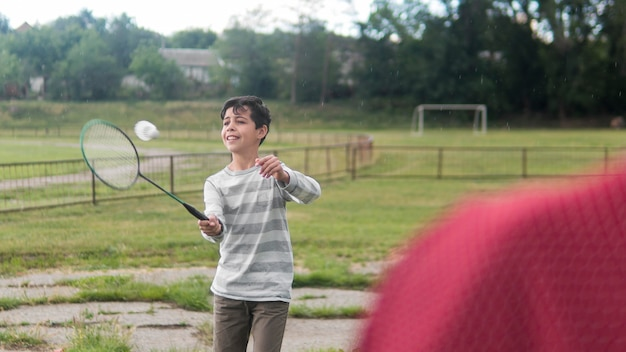 Bambino che gioca a badminton all'aperto