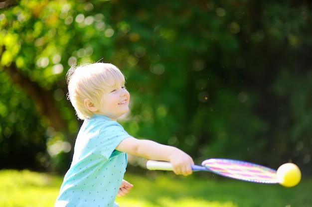 Bambino che gioca a badminton nel parco estivo