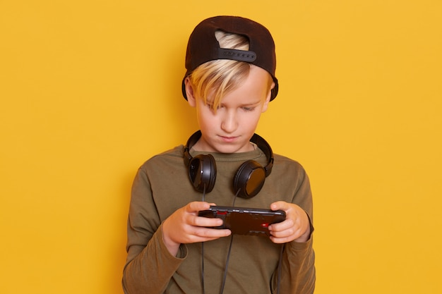 Bambino che gioca a giochi online, ragazzino con dispositivo digitale, bambino maschio indossa camicia verde e berretto con le cuffie