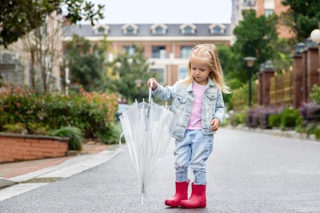 Bambino che gioca all'aperto sotto la pioggia