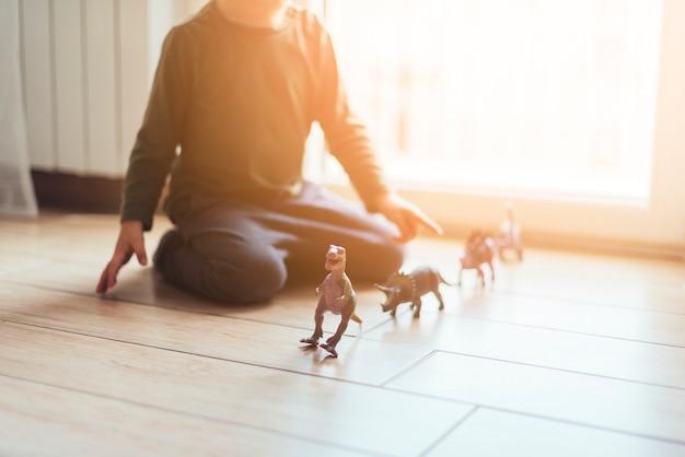 Bambino che gioca con dinosauri giocattolo