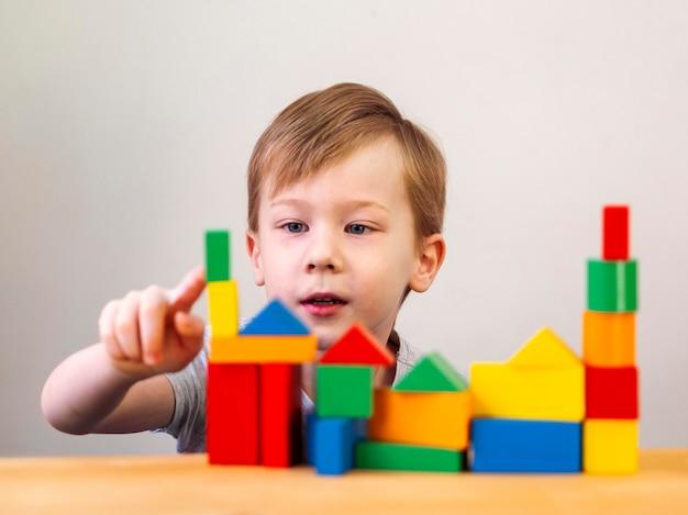 Bambino che gioca con diverse forme colorate