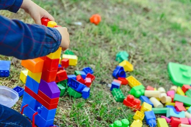 Bambino che gioca con i blocchi colorati che si siedono sulla terra di un giardino in primavera, spazio negativo.