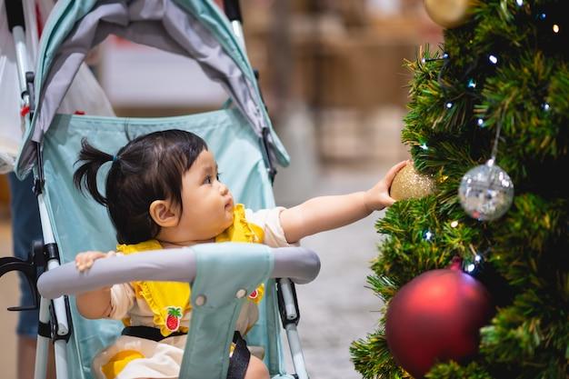 Bambino che gioca con la palla e l'albero di pino di natale