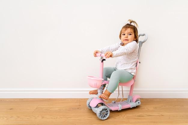 Bambino che gioca con lo scooter a casa in salotto