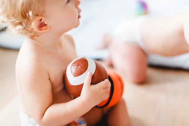 Bambino che gioca con palloni sportivi