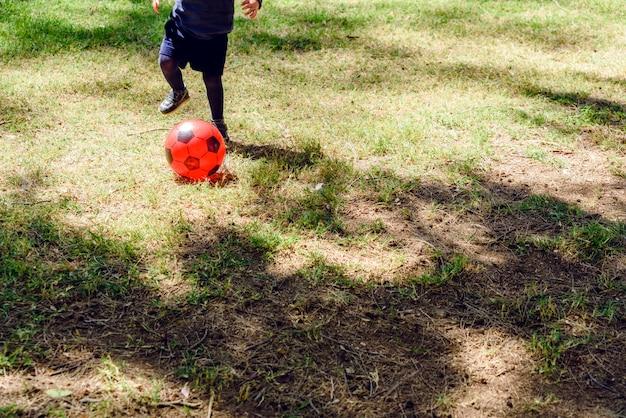 Bambino che gioca con una palla di calcio di plastica rossa.