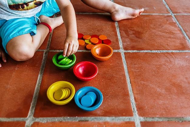Bambino che gioca con una serie di ciotole colorate per riempirle, mentre impara a contare manipolando il materiale educativo.