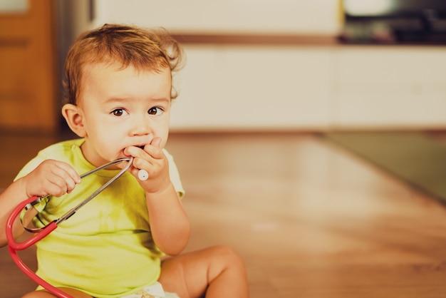 Bambino che gioca con uno stetoscopio medico sul pavimento della sua casa, concetto di pediatria.