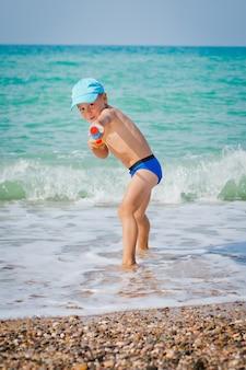 Bambino che gioca in mare con pistola ad acqua
