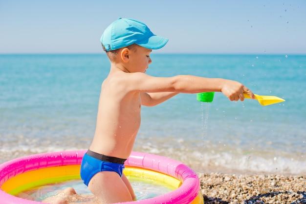 Bambino che gioca in mare con una pistola d'acqua