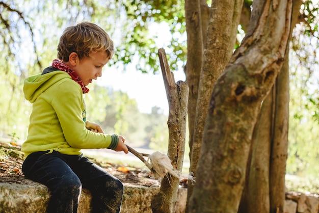 Bambino che gioca liberamente nell'apprendimento della natura in una scuola forestale, nuova educazione alternativa.