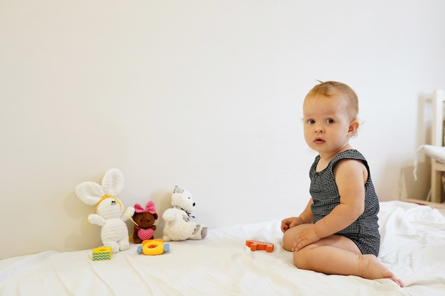 Bambino che gioca piccolo bambino che gioca con i giocattoli a casa, stanza luminosa, copia spazio