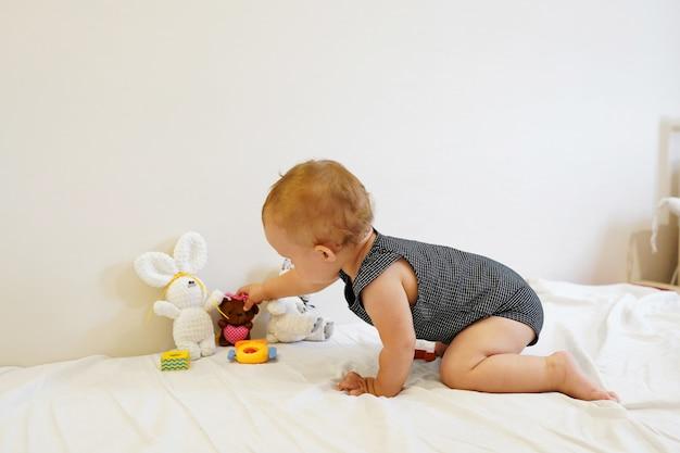Bambino che gioca piccolo bambino che gioca con i giocattoli a casa, stanza luminosa