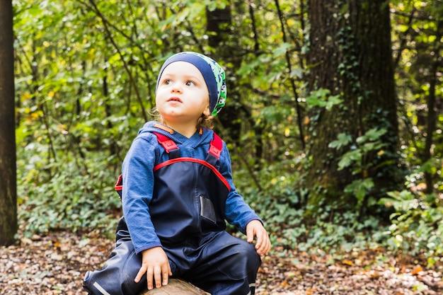 Bambino che gioca su un sentiero nel bosco in autunno