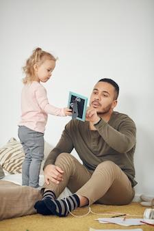 Bambino che guarda le foto con papà