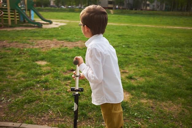 Bambino che impara a guidare uno scooter in un parco cittadino carino ragazzo in età prescolare casco di sicurezza in sella a un rullo